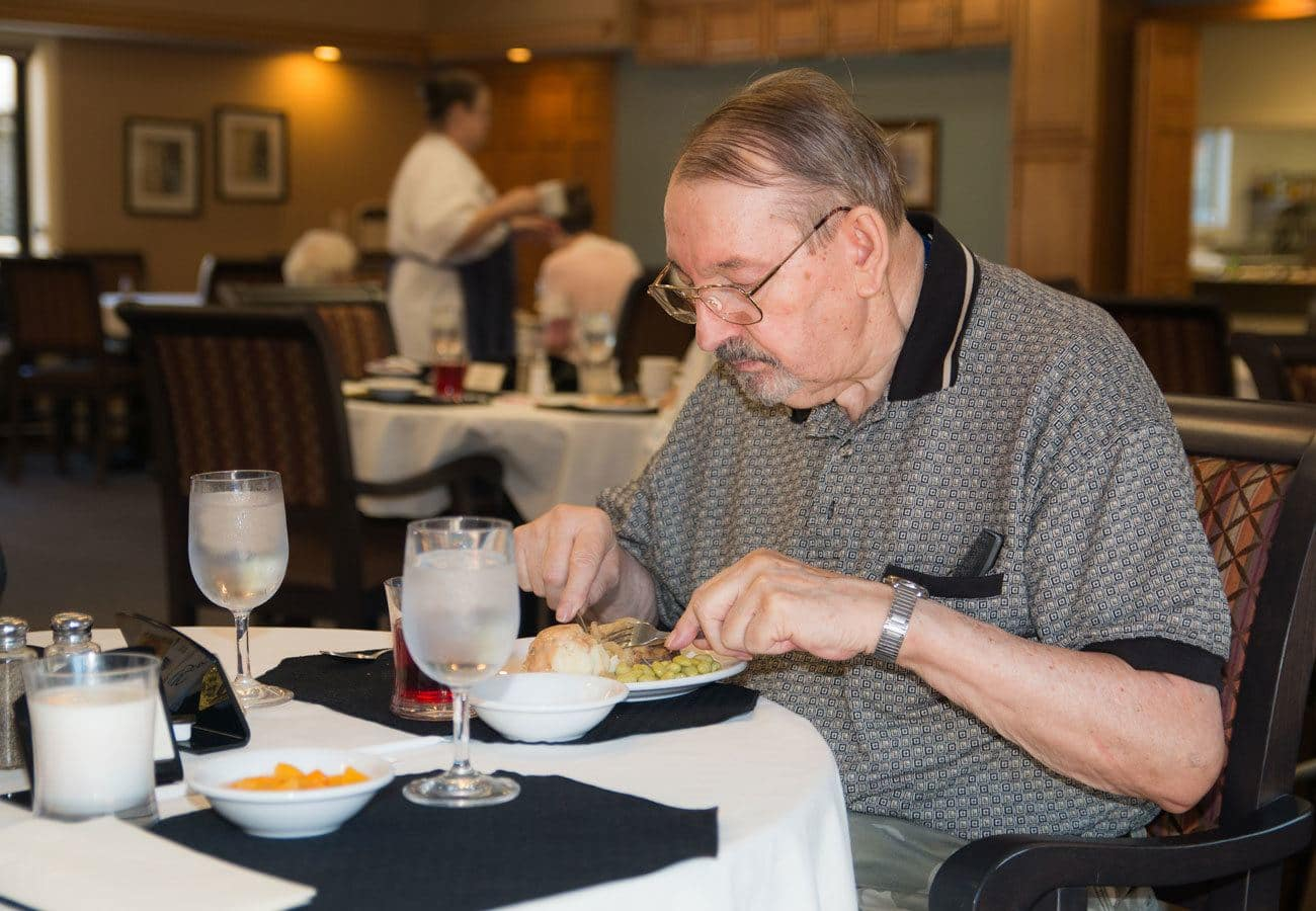 Resident enjoying a meal in the dining hall at White Oaks in Lawton, Michigan