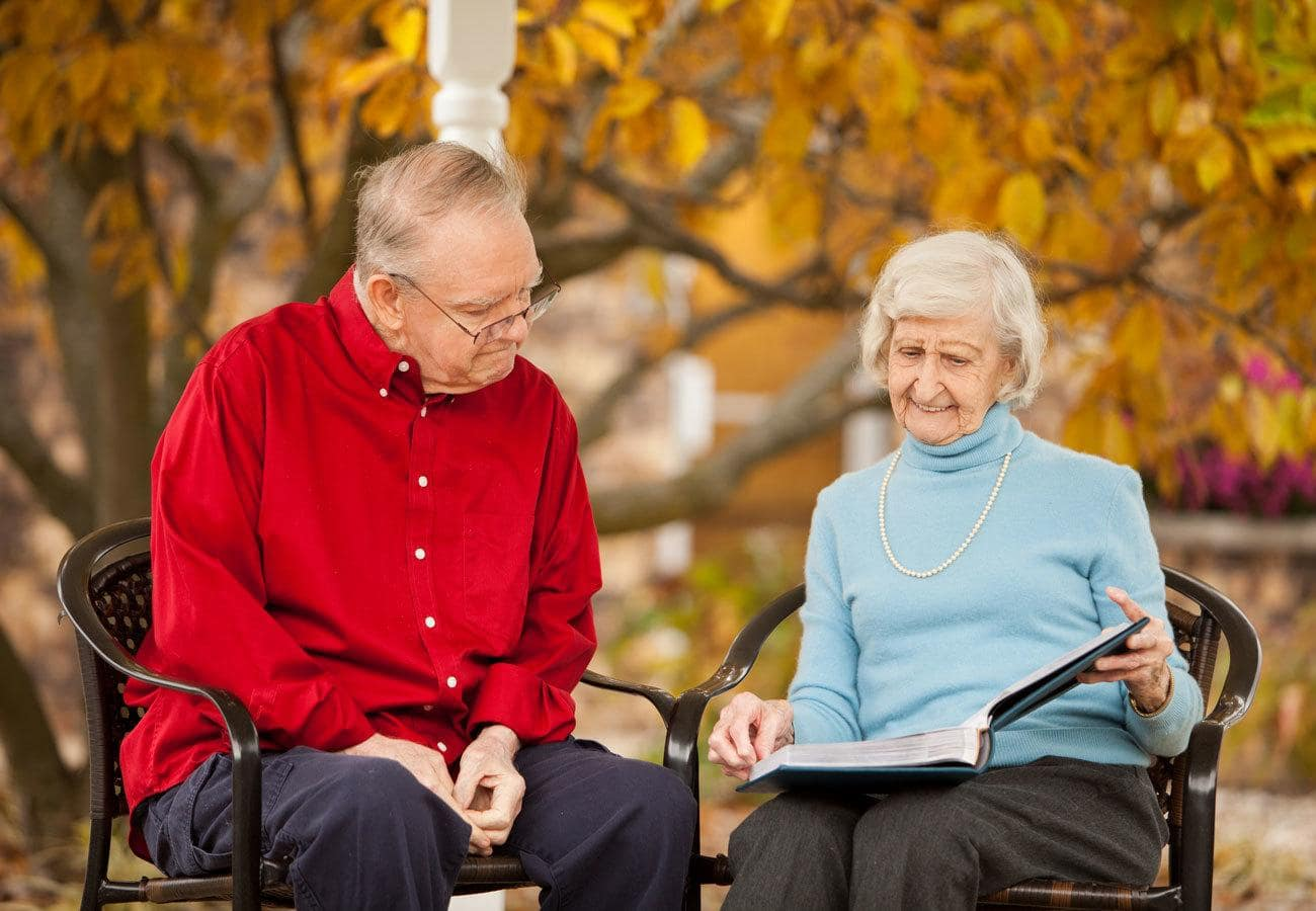 Resident couple reading a book at White Oaks in Lawton, Michigan