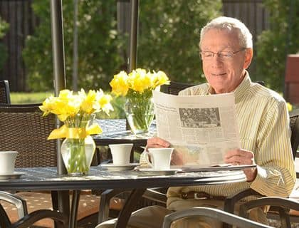 A resident having coffee and reading the paper at Symphony Manor