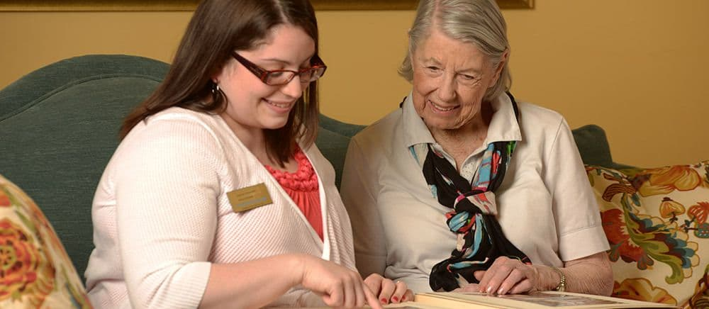 A staff member and resident bond over a memory book at Symphony Manor