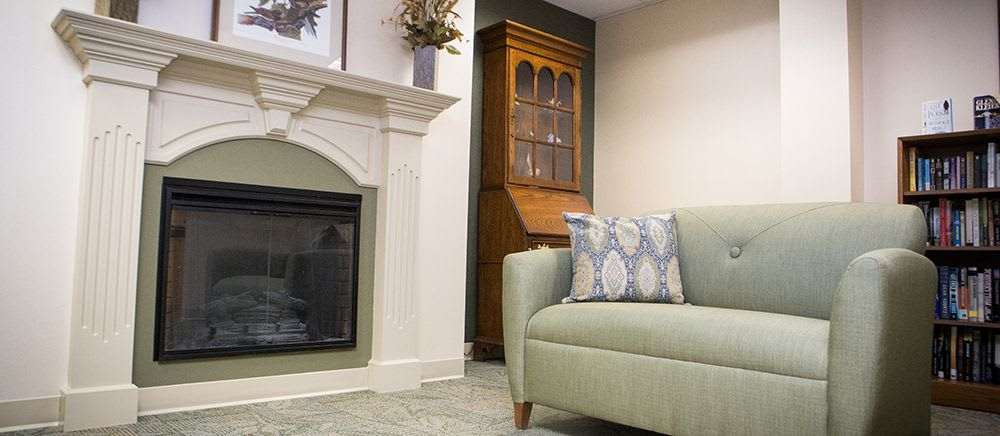 A fireplace and green loveseat at Symphony Manor of Richmond