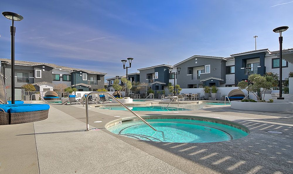 View of the swimming pool area with the hot tub in the foreground at Dream Apartments in Henderson