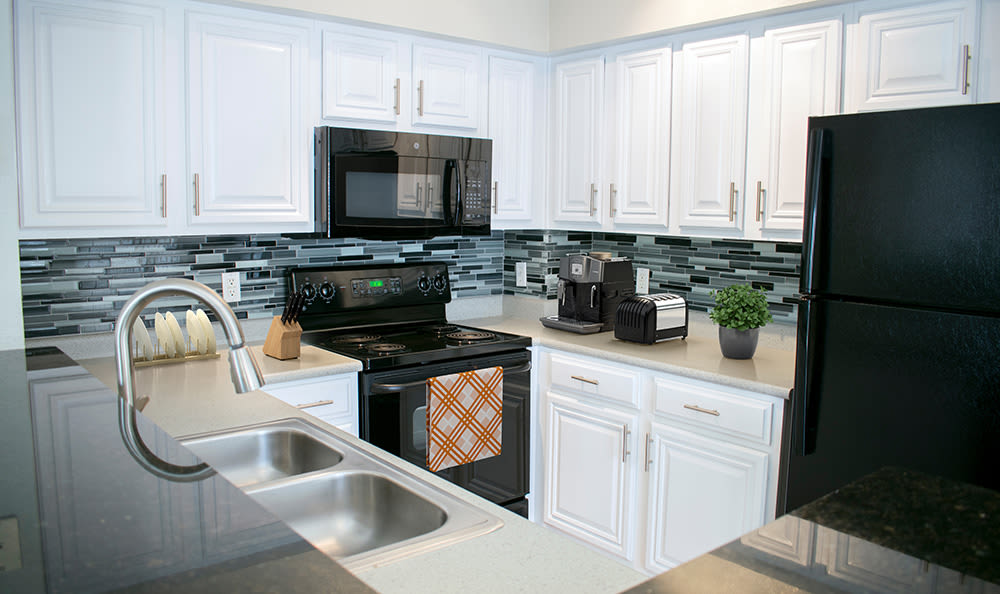 Granite countertops and black appliances in model kitchen at The Estates at Park Avenue in Orlando
