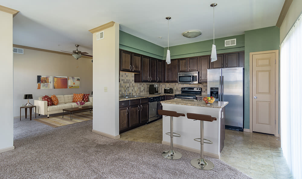 View of living area and kitchen from dining area in model home at West End at City Center in Lenexa