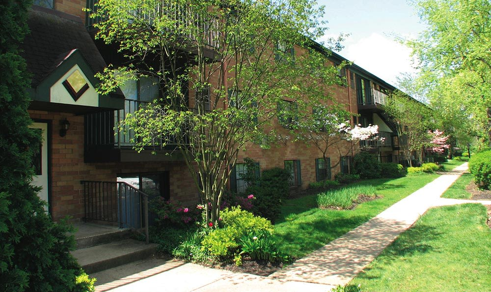 Exterior resident building view showcasing well-maintained landscaping at Cedarwood Village Apartments in Akron