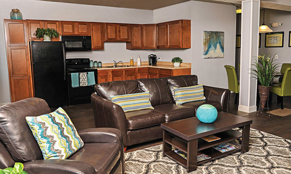 Kitchen and living room view at Webster Manor Apartments home in Webster