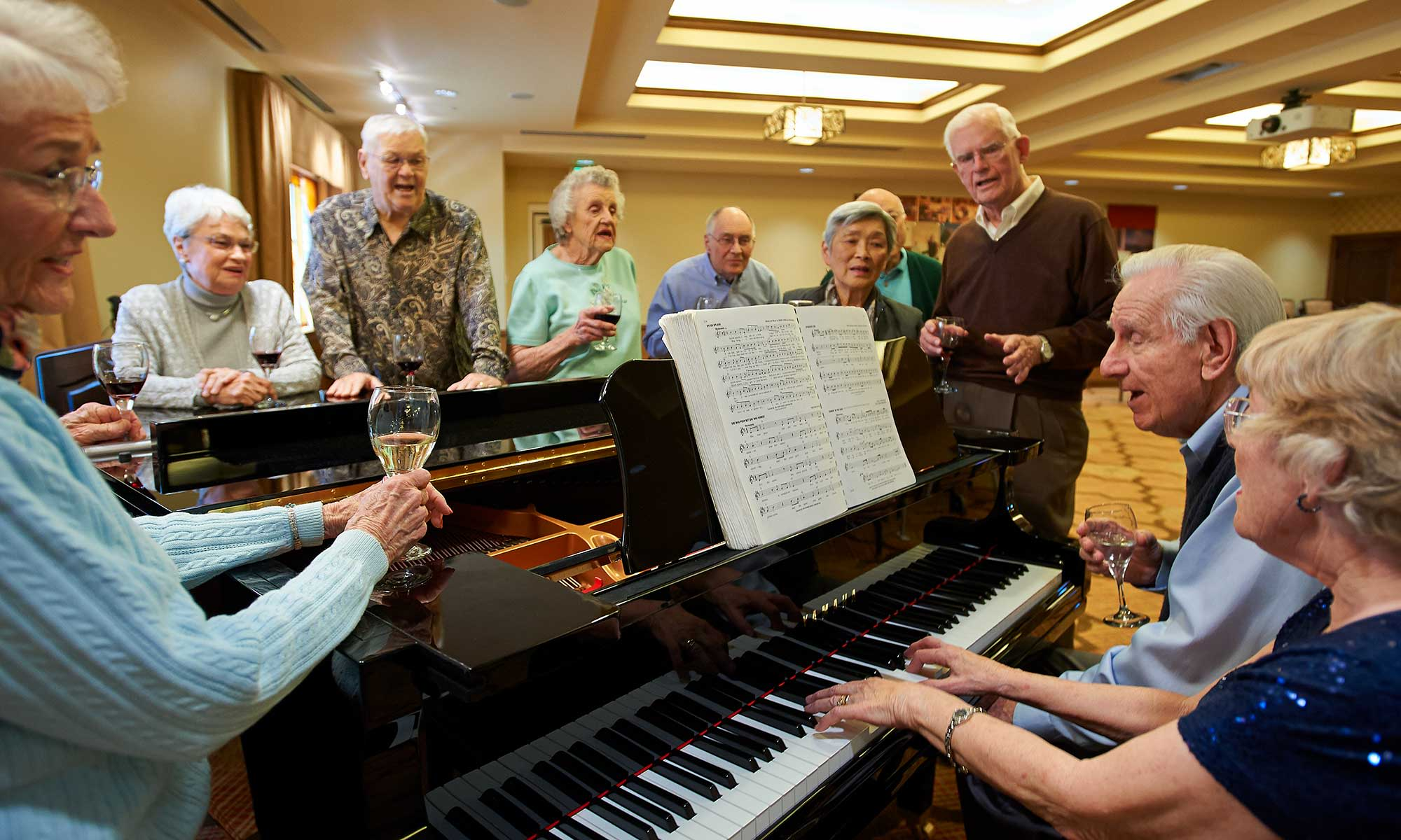 Residents singing around the piano at Clermont Park in Denver