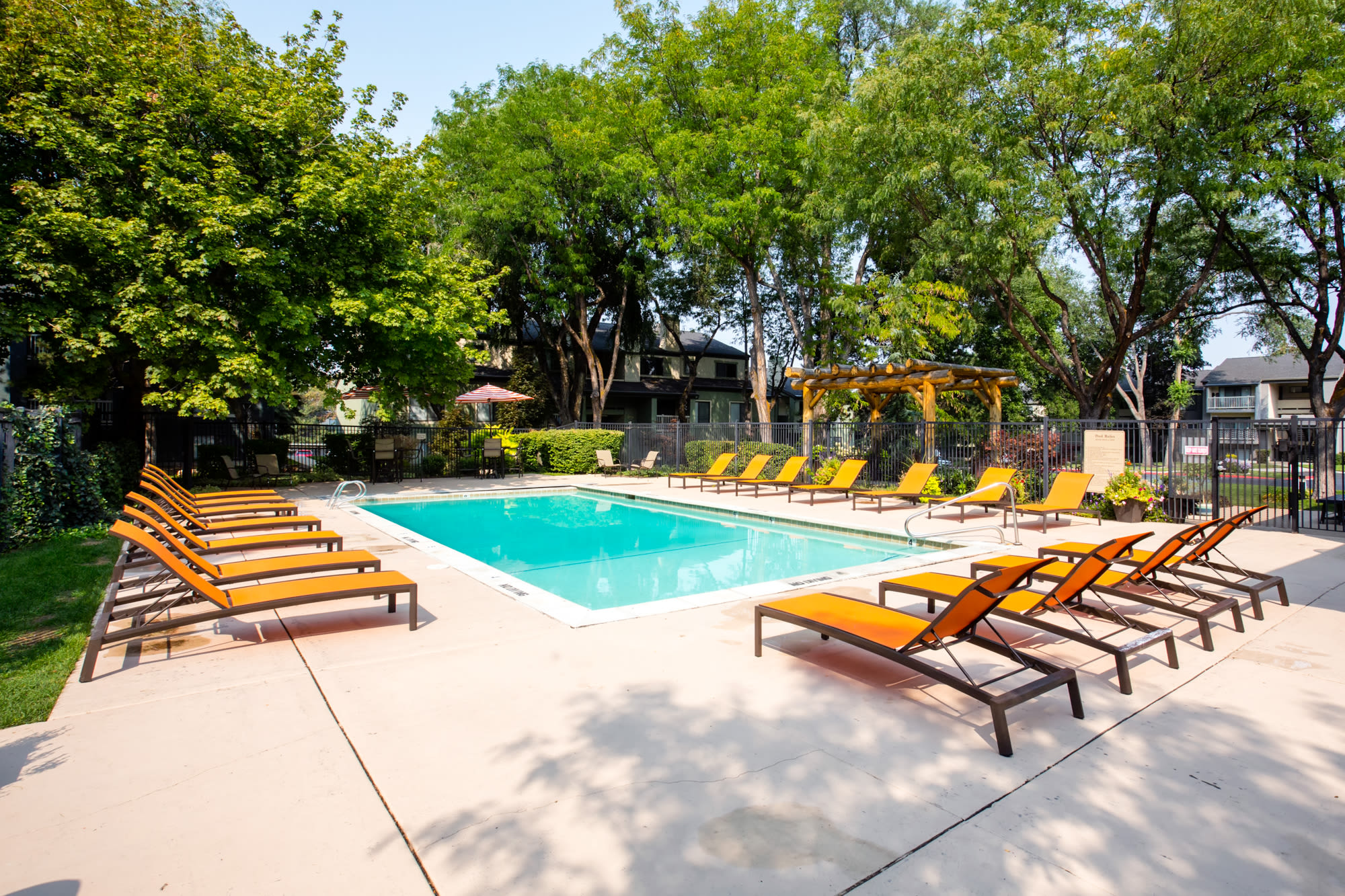 Pool Surrounded by Lounge Chairs and Lush Landscaping in Salt Lake City, UT