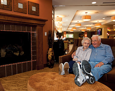 Resident couple at Clermont Park relaxing in front of the fireplace in one of the comfortable common areas