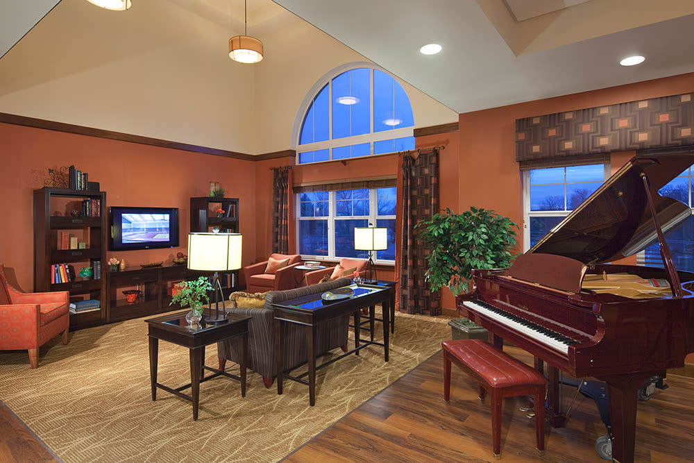 Grand piano and comfortable seating in common area at Clermont Park in Denver