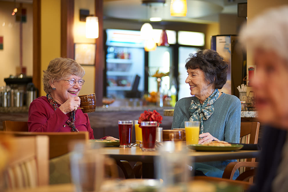 Residents enjoying a beverage in the restaurant at Clermont Park in Denver