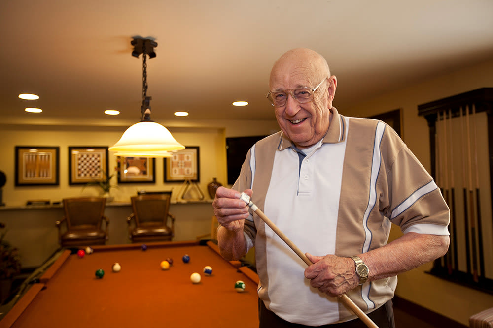 Resident chalking his cue for a billiards game at Clermont Park