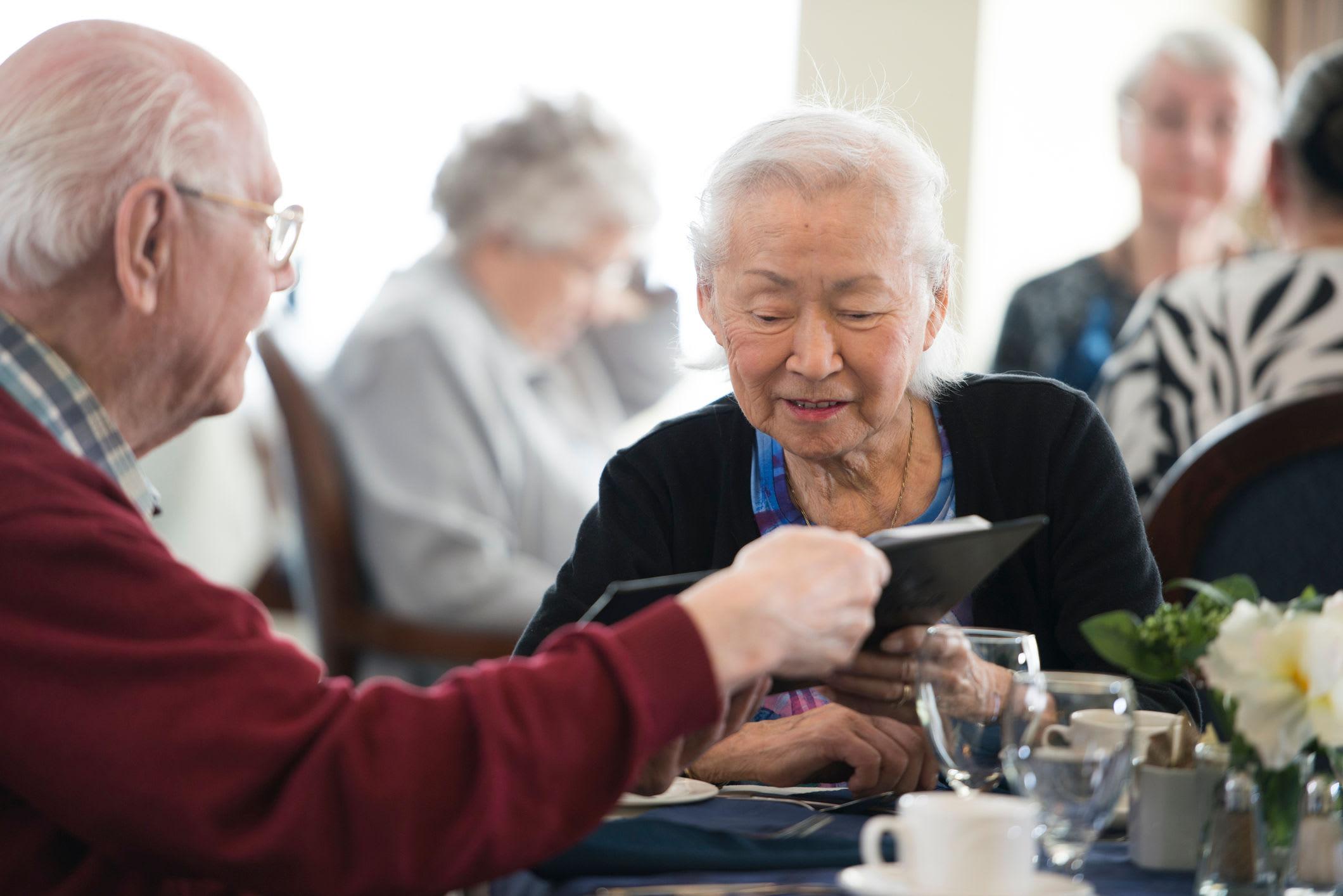 Elderly couple reading the Comfort Residence menu for dinner.