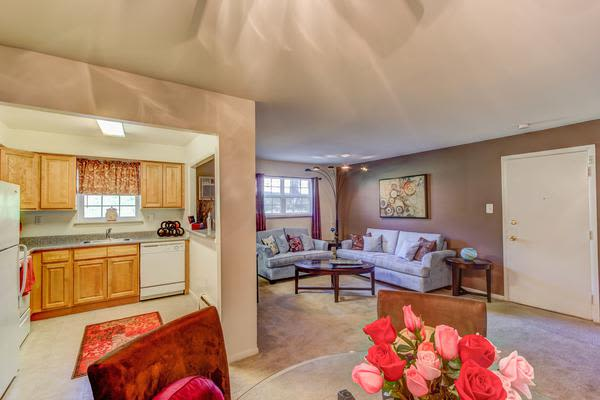 A living room and kitchen that are great for entertaining at Woodacres Apartment Homes in Claymont, DE