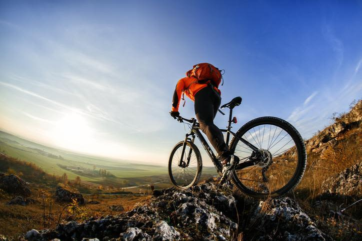 fish-eye photo of mountain bike rider with red jacket, red backpack, and black pants riding over rocky terran above a valley with mostly blue sky