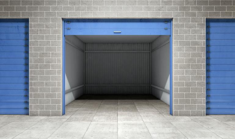 Open self storage unit made of grey bricks with blue door