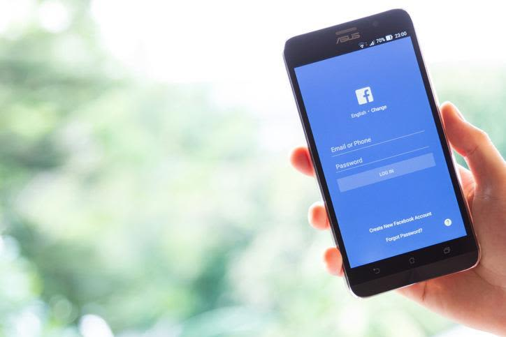 Photo of Asus smartphone with facebook app login screen being held by a hand against a blurred green vegetation background