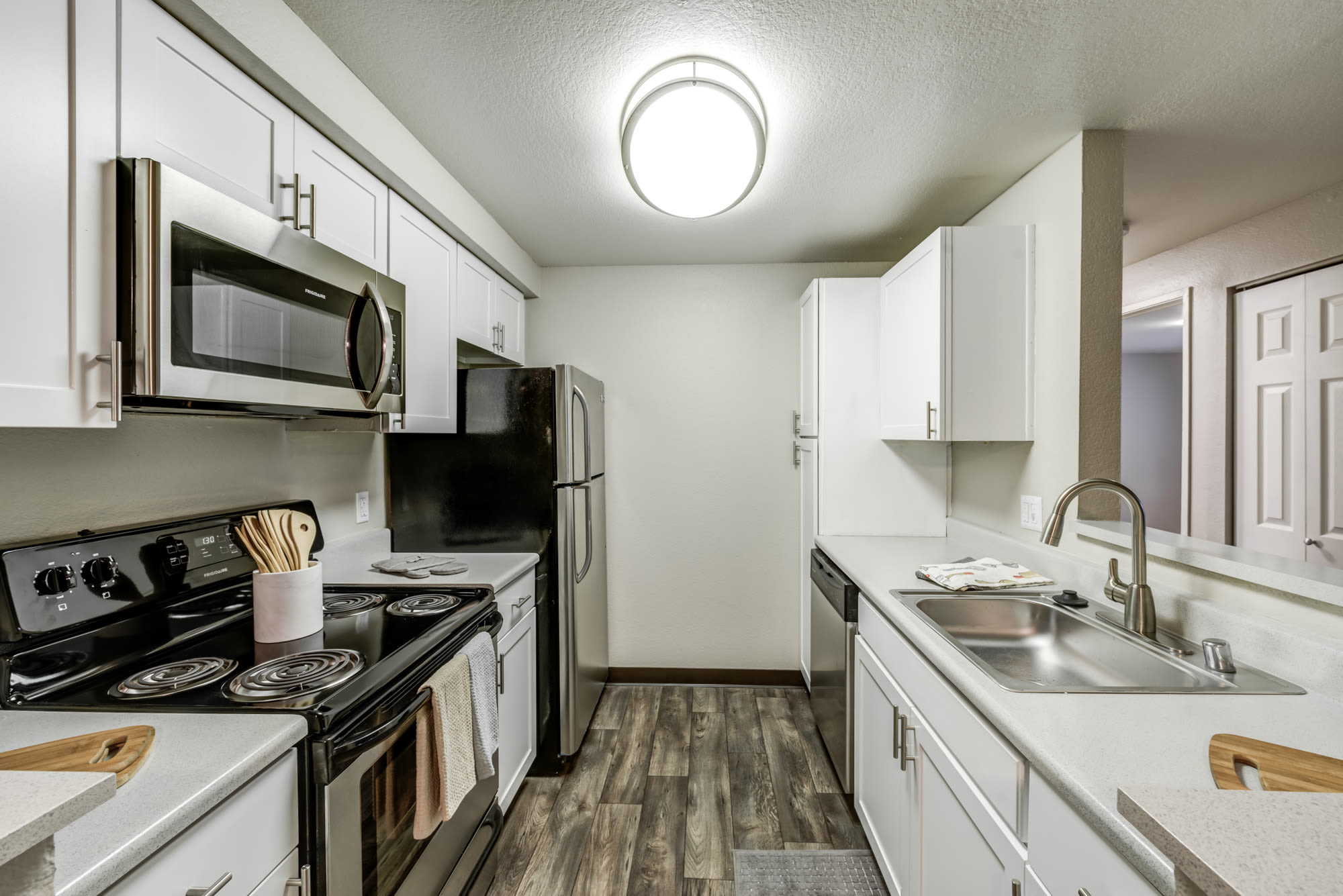 White renovated kitchen with stainless steel appliances at Olin Fields Apartments in Everett