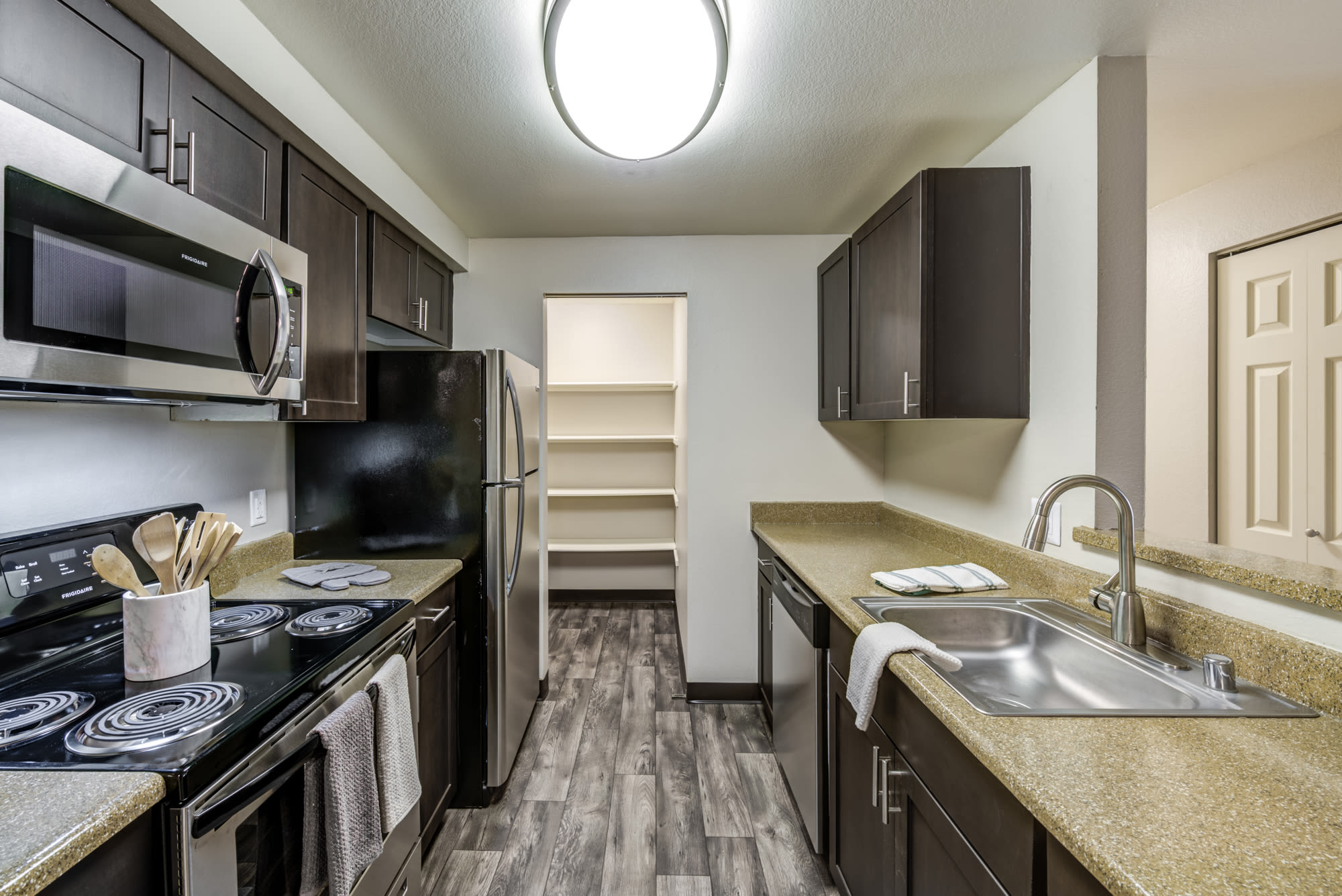 Brown renovated kitchen with stainless steel appliances at Olin Fields Apartments in Everett