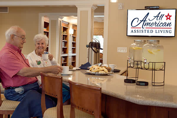A couple enjoying coffee and snacks at All American Assisted Living at Washington Township