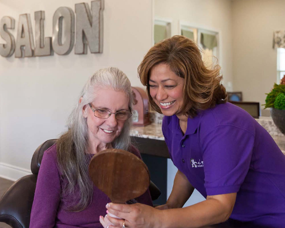 Staff member assisting resident in the salon at Iris Memory Care of Turtle Creek in Dallas, Texas.