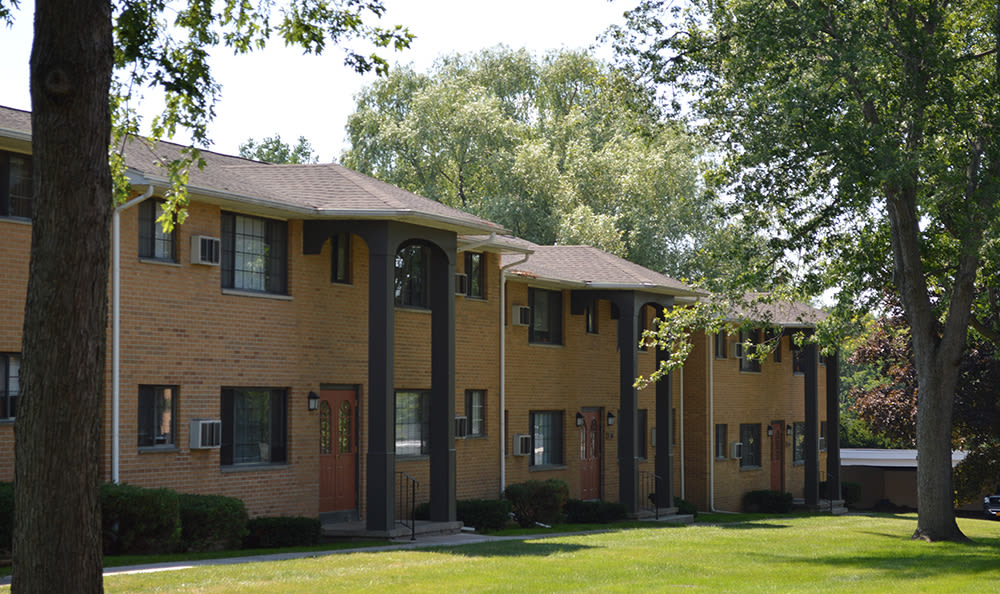 Exterior view of apartment building at Creek Hill Apartments & White Oak Apartments in Webster, NY