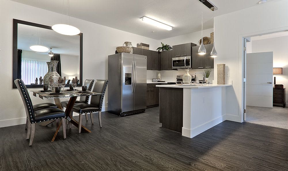 View of dining and kitchen areas from living room in model apartment home at Union Apartments in Las Vegas