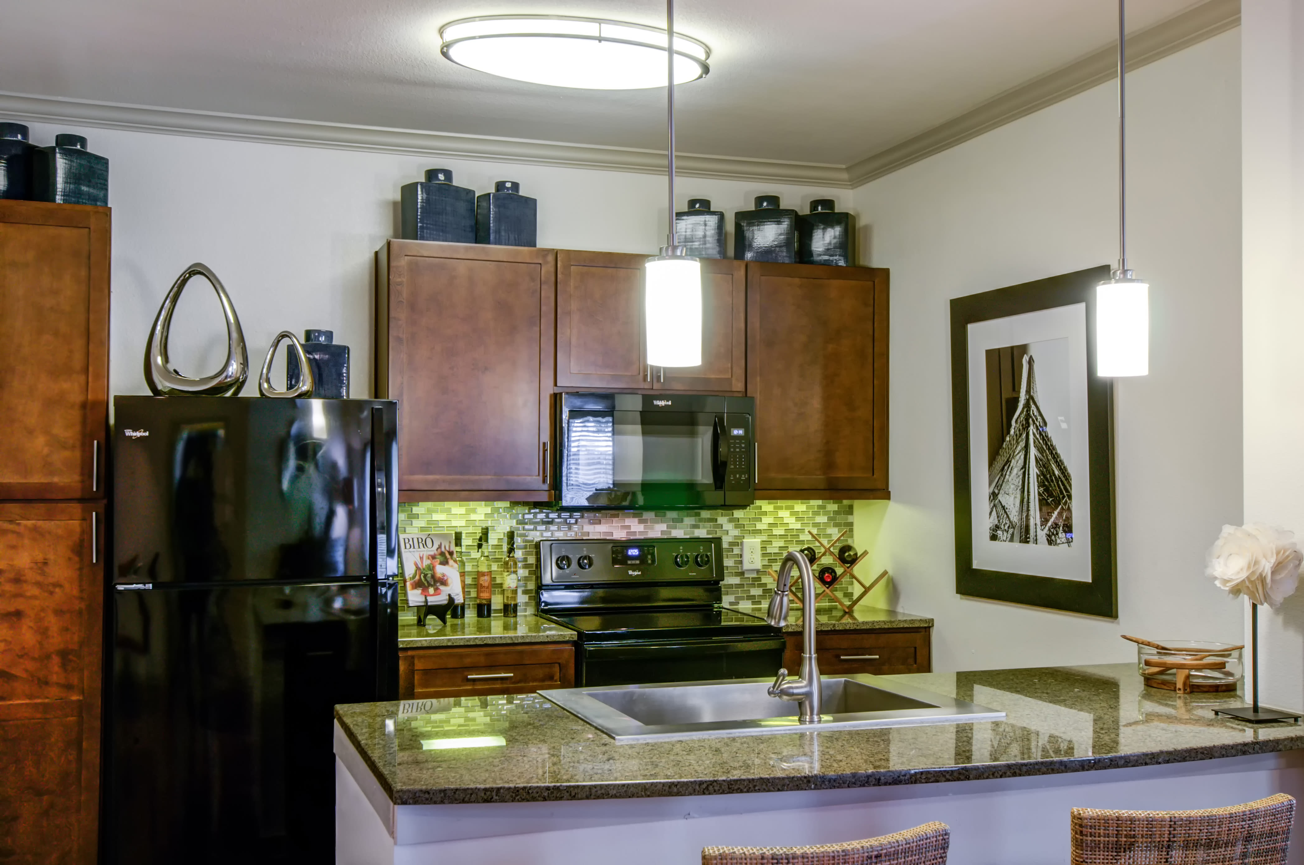 Granite countertop kitchen with bar seating at Firewheel Apartments in San Antonio