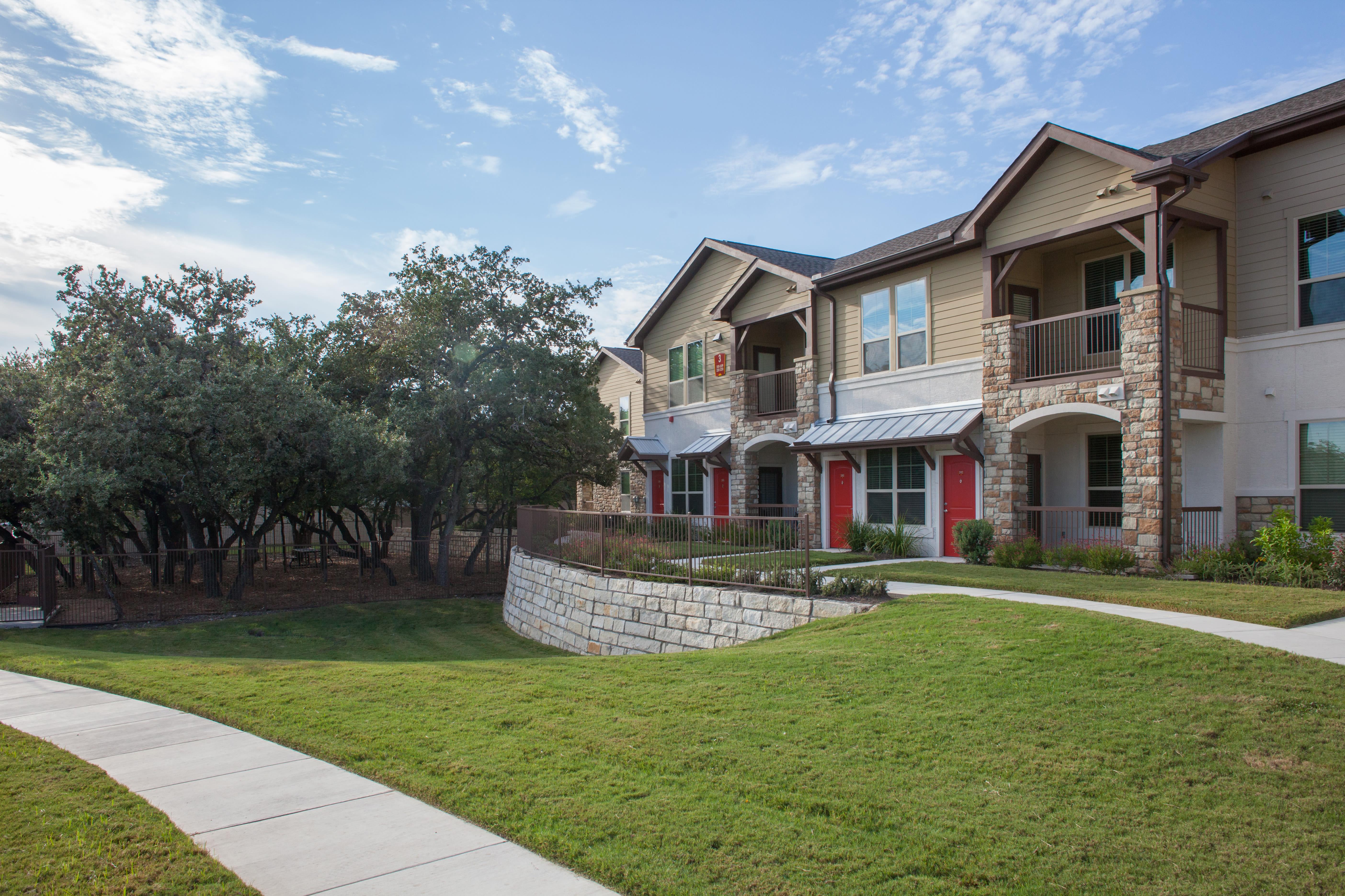 Lawn space and sidewalks outside at Firewheel Apartments in San Antonio