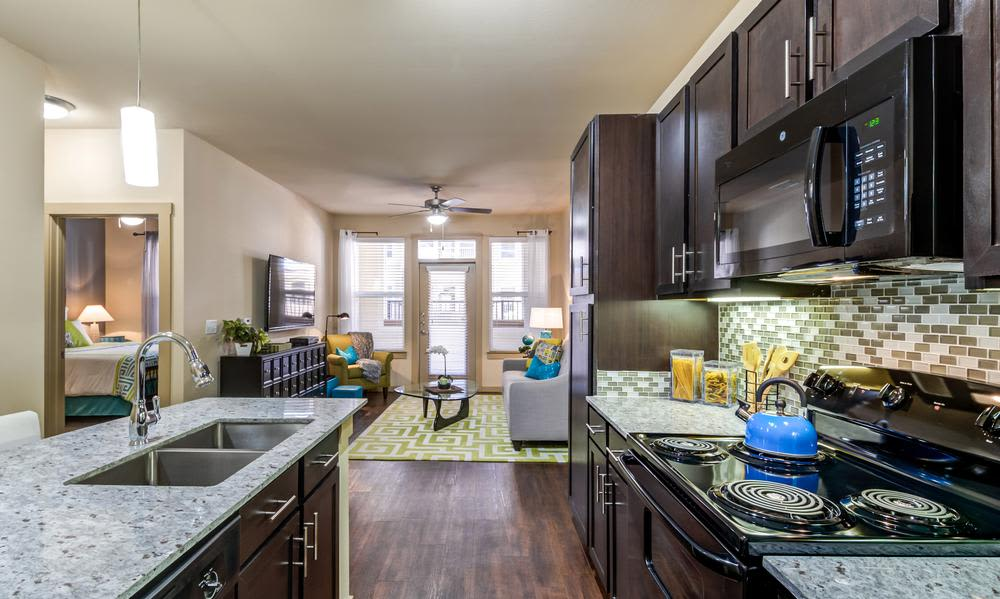 View of the kitchen - showcasing rich, dark wood cabinetry - in model home at 4000 Hulen Urban Apartment Homes