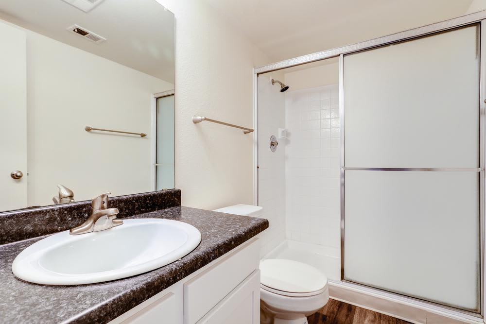 Bright bathroom with walk in shower at Deerfield Apartments in Denver, CO