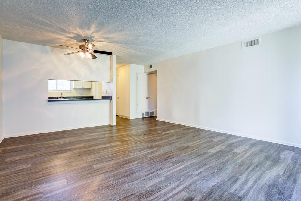 Spacious living room with ceiling fan at Deerfield Apartments in Denver, CO