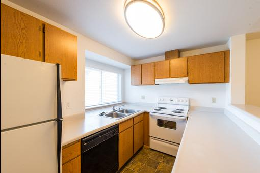 Model kitchen with white appliances at Village at Seeley Lake in Lakewood, Washington