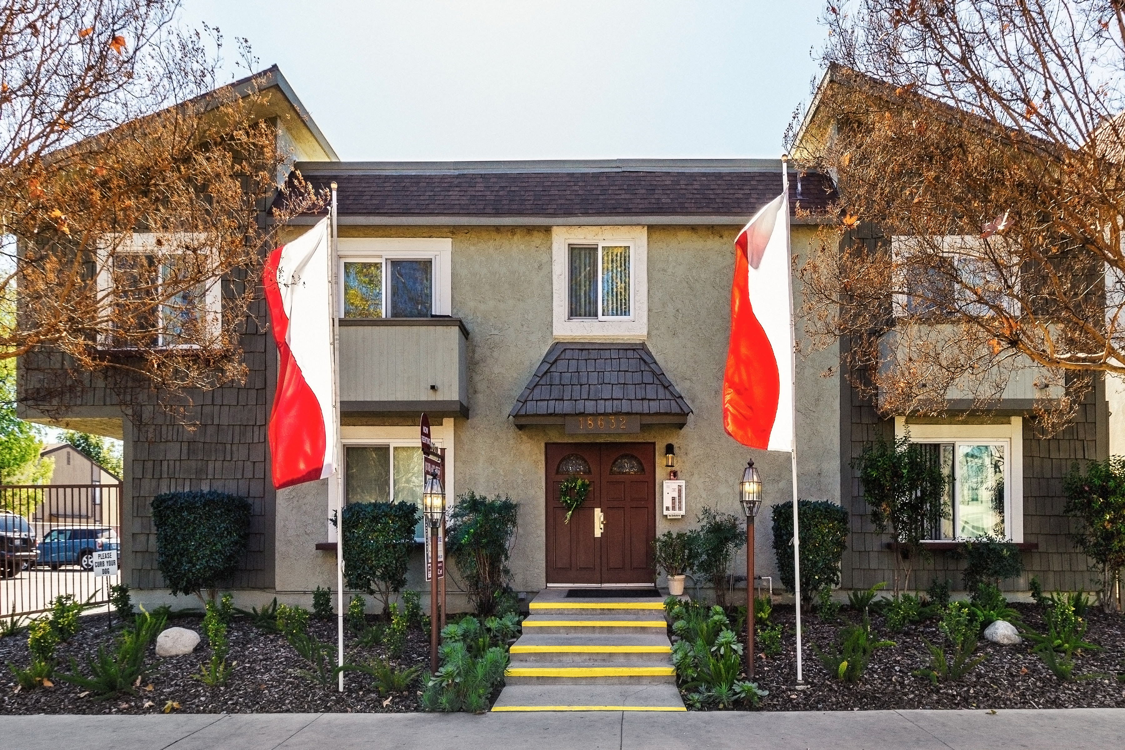 Exterior of building with flags at The Newporter in Tarzana, California