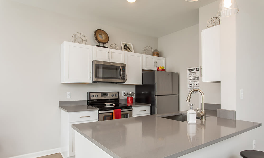 Modern and well-equipped kitchen in Woodland Acres Townhomes model home