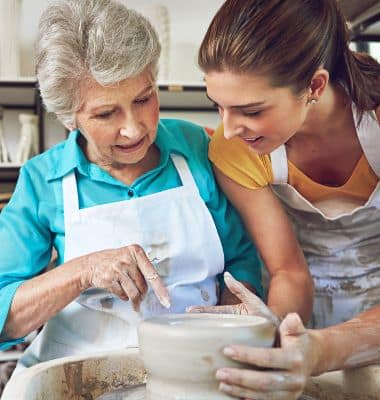 Senior woman preparing food with her daughter at All American Assisted Living at Kingston