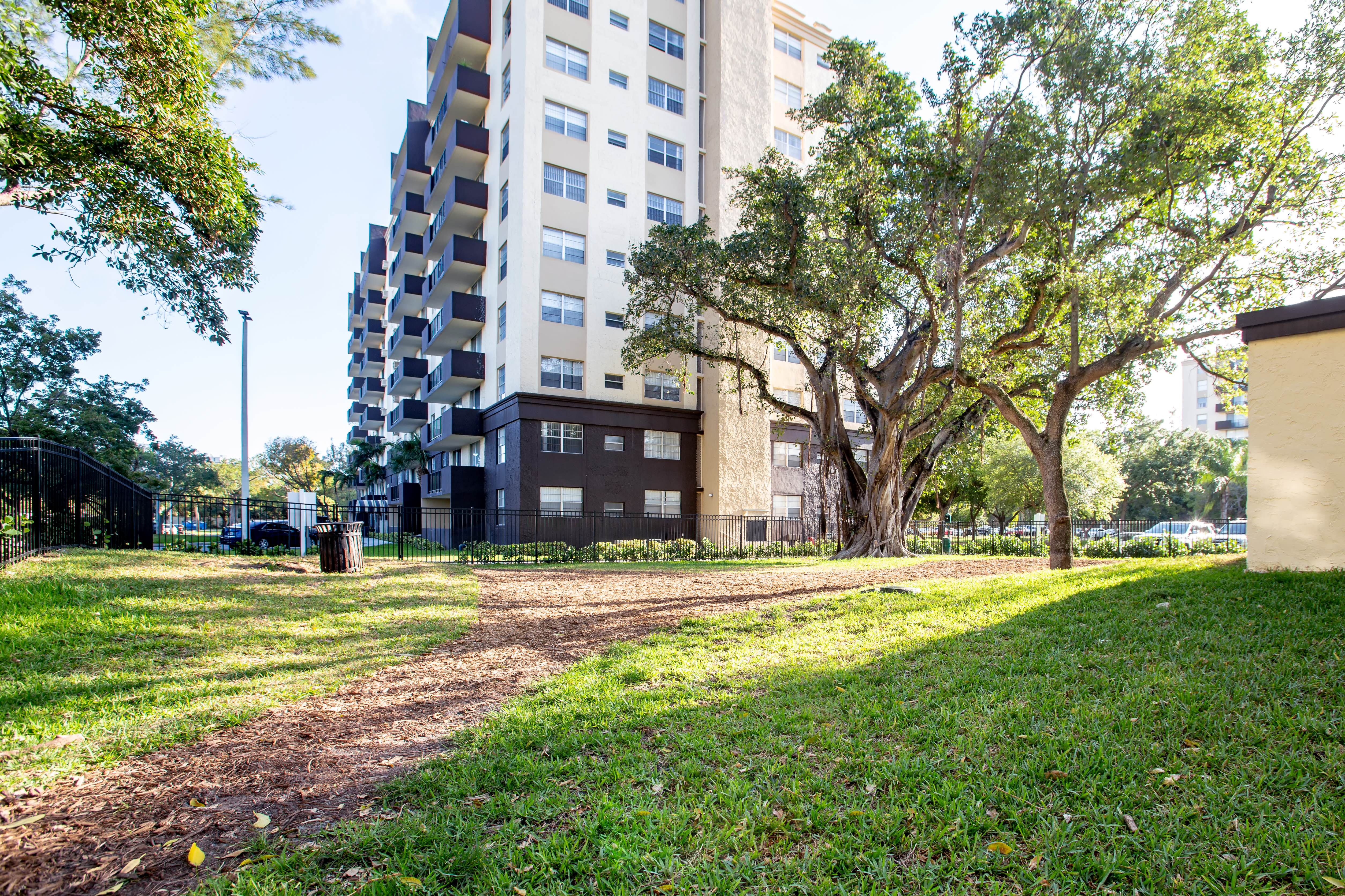 Walking path among well-manicured landscaping and mature trees at Aliro Apartments in North Miami, FL