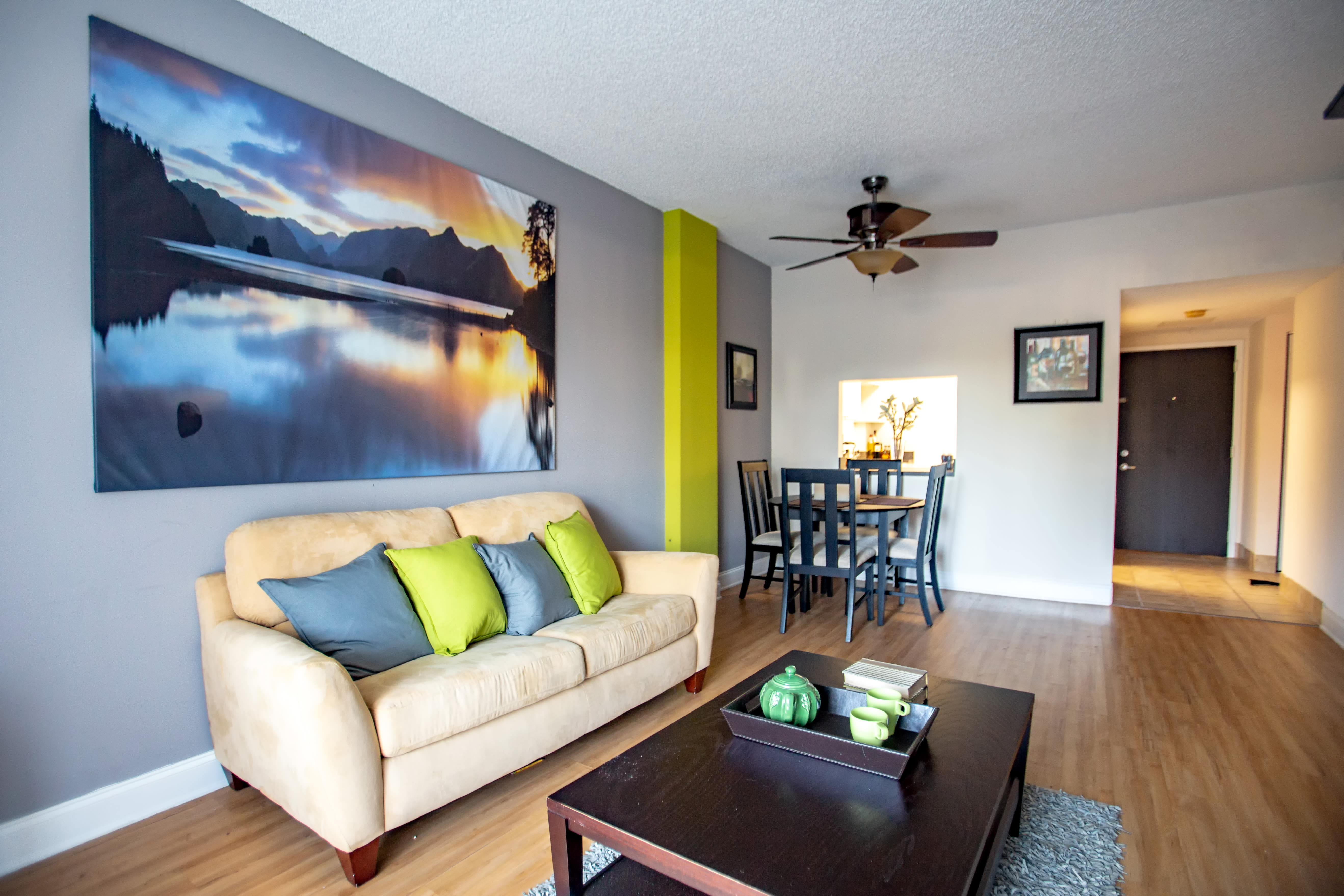Modern decor, hardwood floors, and ceiling fan in model home's living room at Aliro Apartments in North Miami, FL
