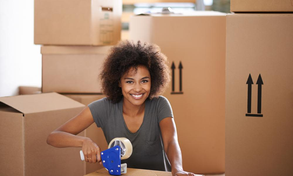 Woman packing a box to store at A Better Self Storage Bott in Colorado Springs Colorado