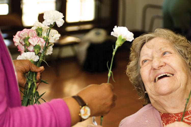 Senior living resident being given a flower at Discovery Commons in Bonita Springs, Florida