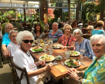 Happy friends eating lunch out and about at the senior living in Grass Valley