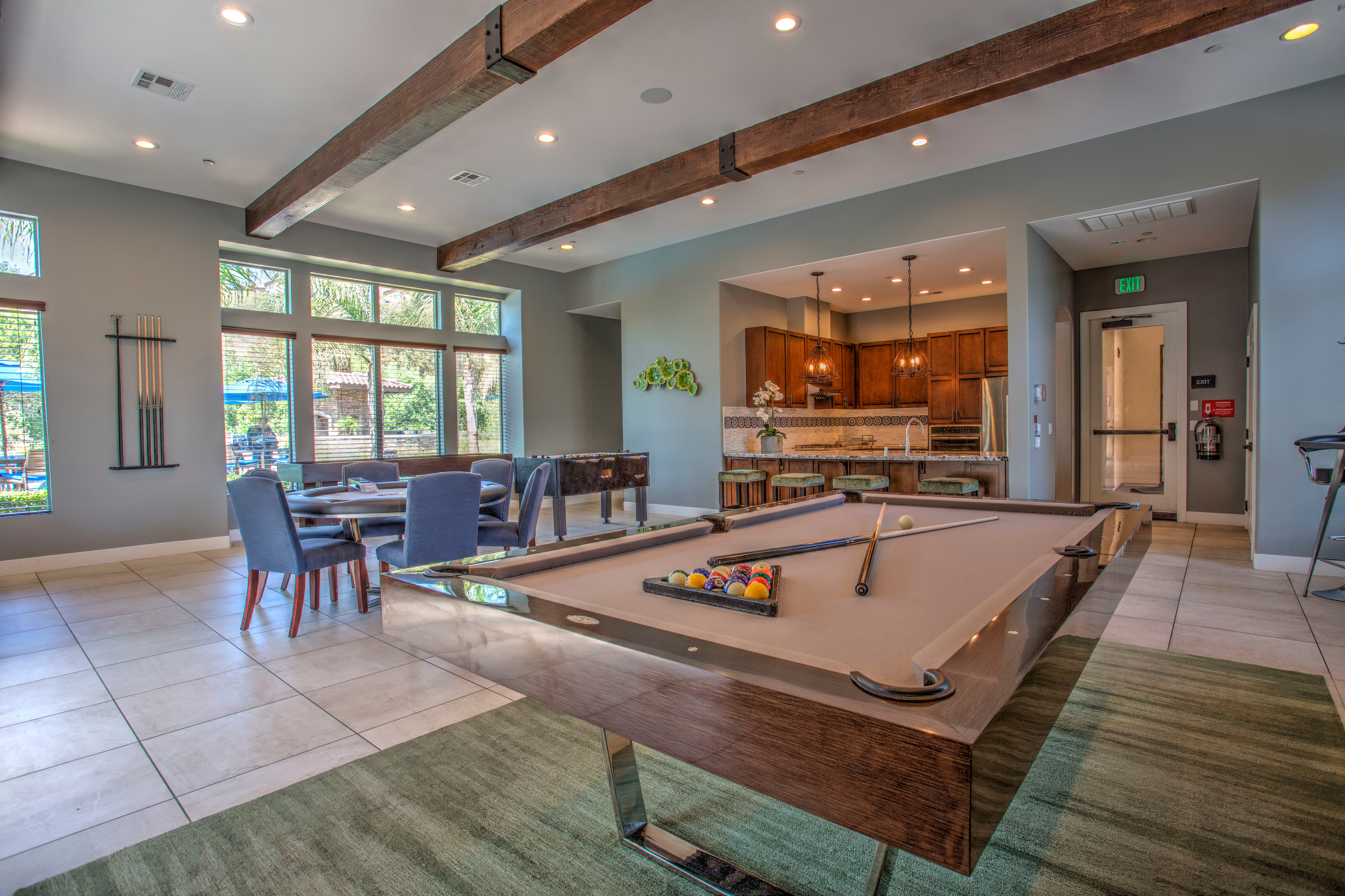 A commons area with a bar, pool, cardtable, foosball, and shuffleboard at Palisades Sierra Del Oro in Corona, California