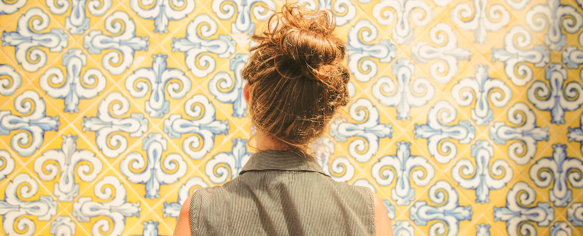 Girl in front of patterned wall paper at The Copeland in Austin, Texas