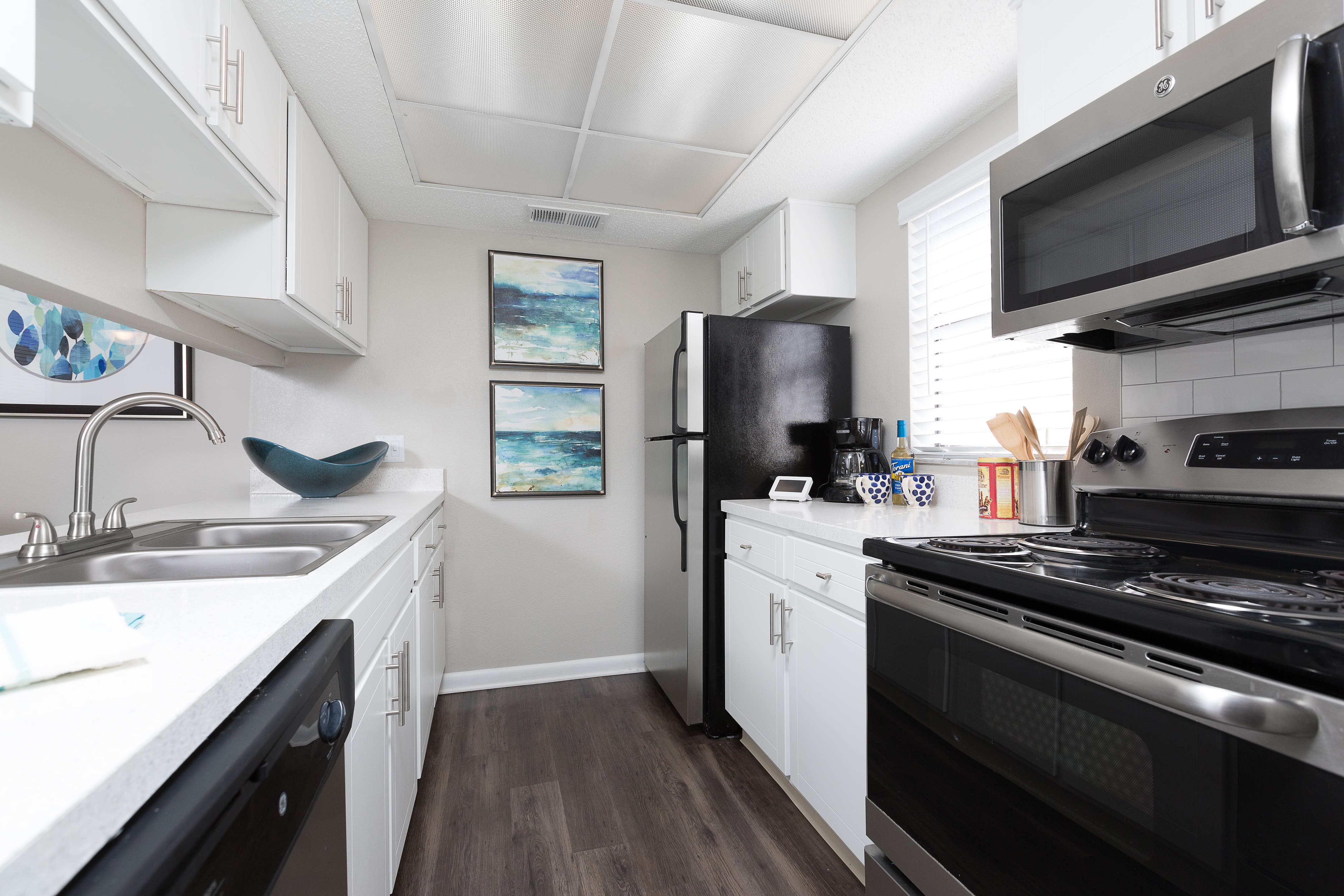Modern kitchen with stainless steel appliances and granite countertops at WestEnd At 76Ten in Tampa, Florida
