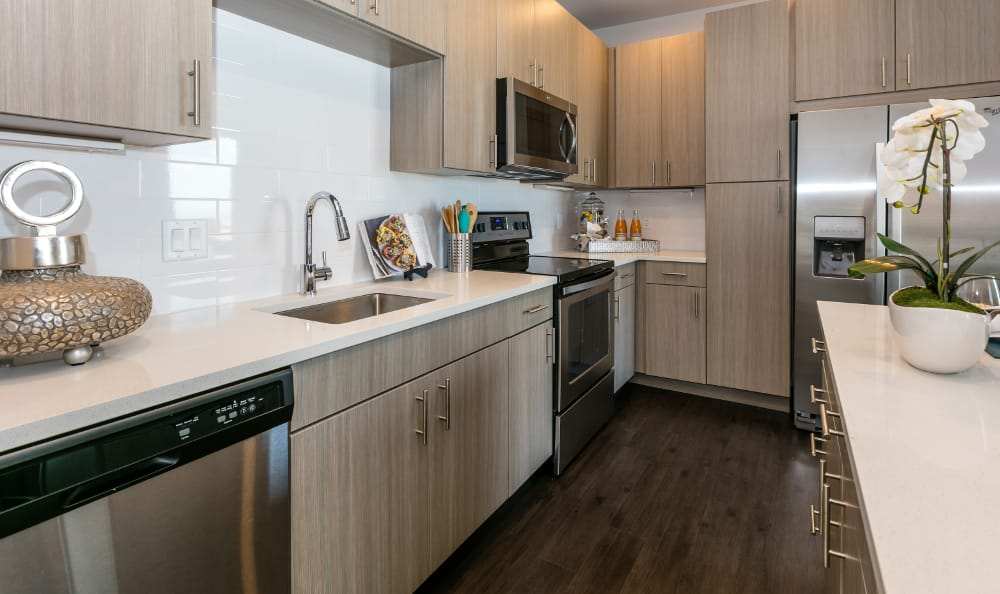 Tan cabinetry Kitchen with stainless steel appliances at Strata Apartments in Denver, Colorado