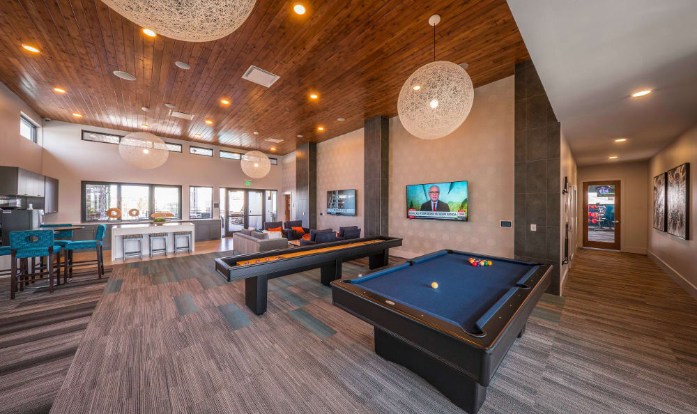 Pool table, game lounge area with TVs at Strata Apartments in Denver, Colorado