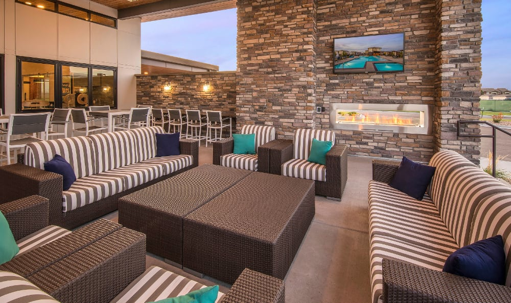 Exterior lounge and BBQ area with TVs and cushioned seating at Strata Apartments in Denver, Colorado