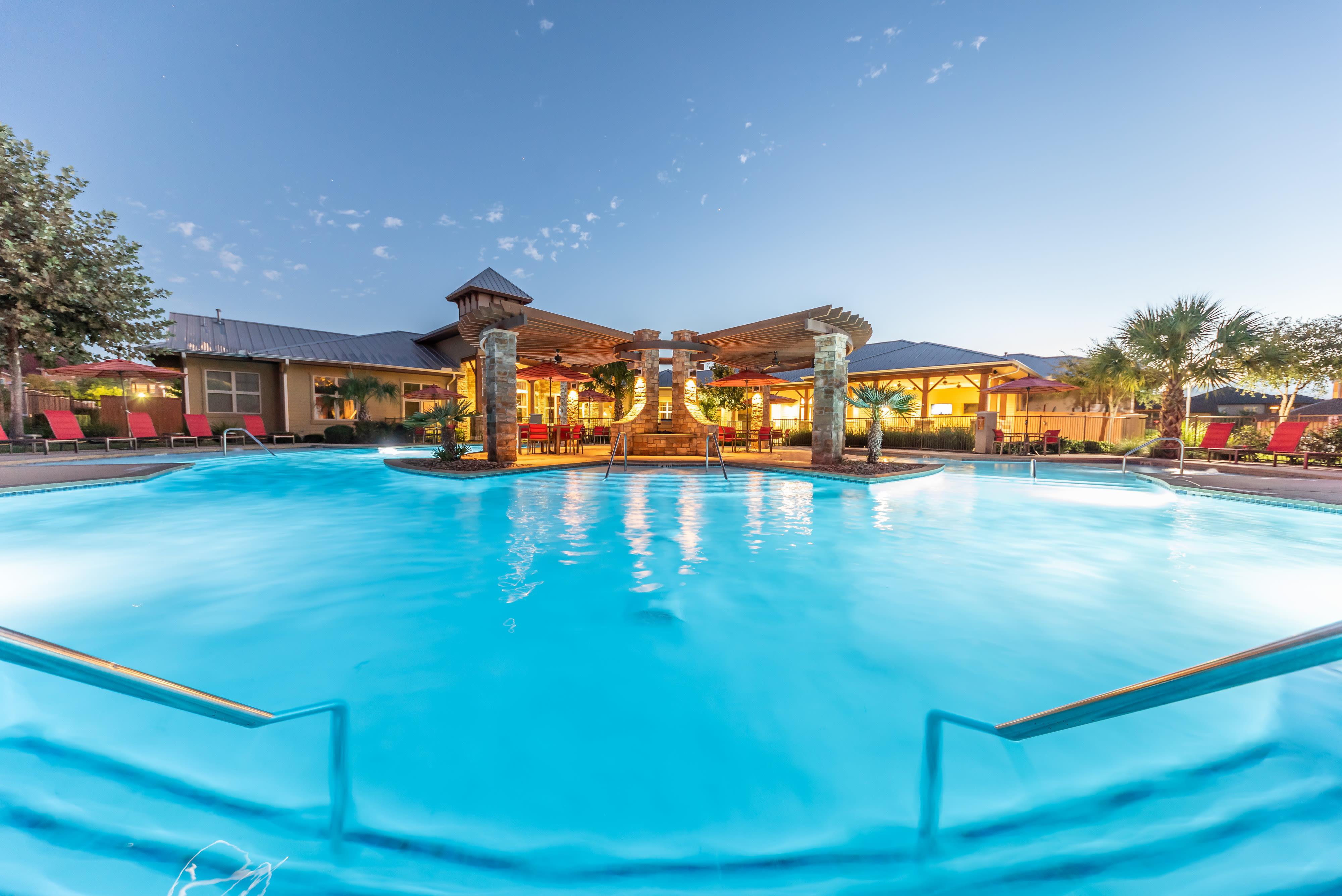 Outdoor pool at dusk at Firewheel Apartments in San Antonio