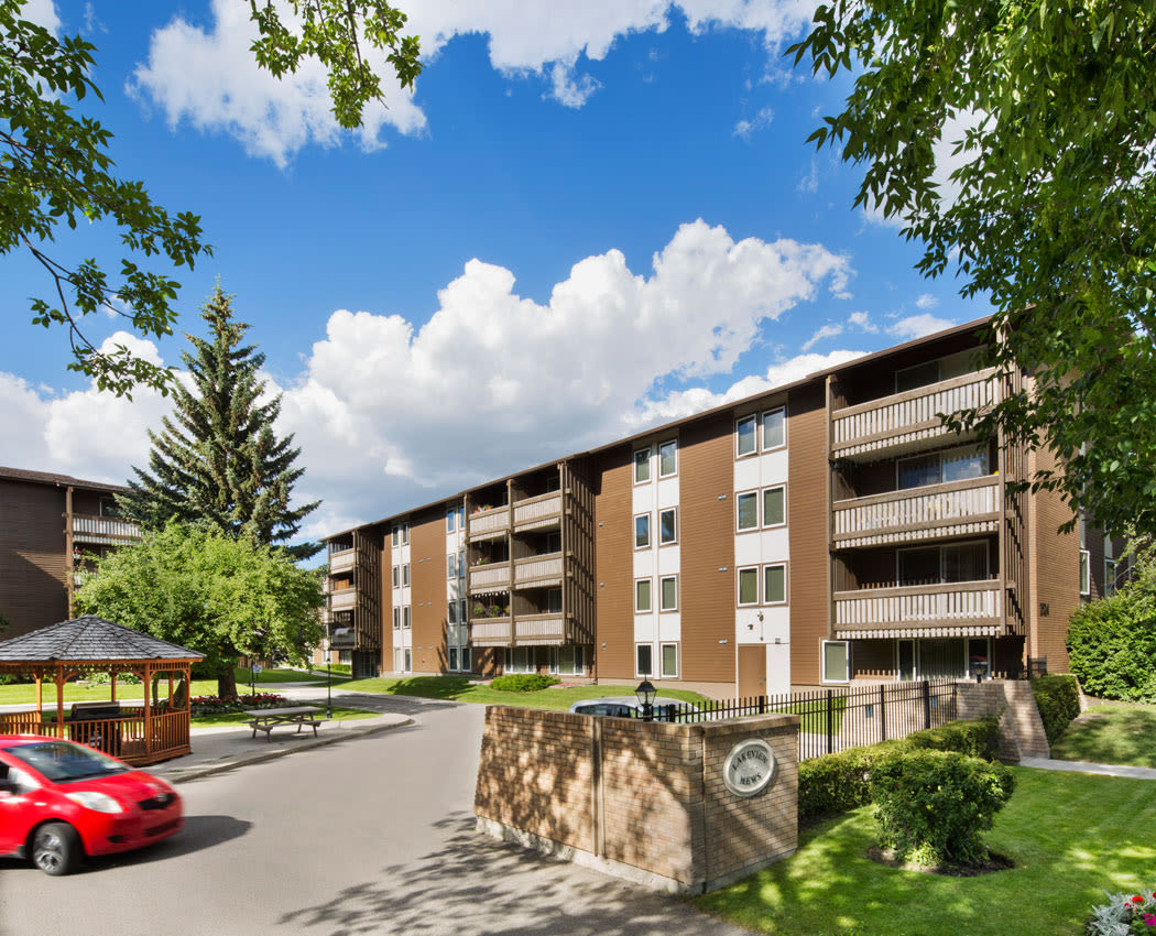 Exterior view of entrance and parking at Lakeview Mews in Calgary, AB
