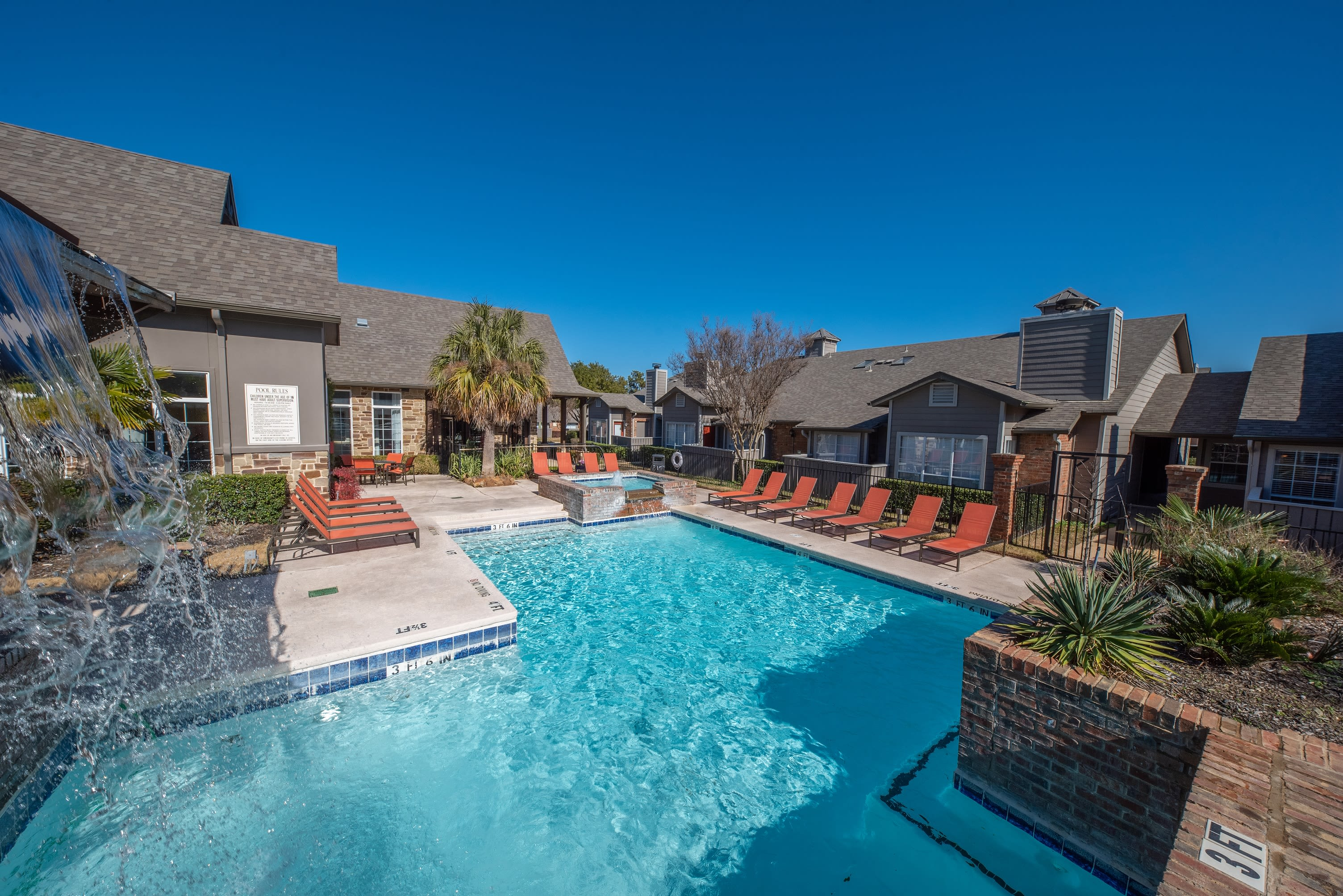 Resort style pool with lounge chairs at Village Green of Bear Creek in Euless, Texas